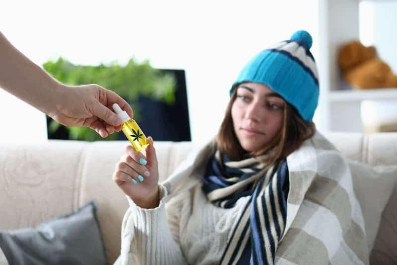Eine Frau nimmt CBD-Öl entgegen
