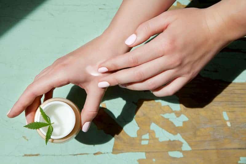 Eine Frau schmiert ein CBD-Kosmetikprodukt auf ihre Handoberfläche